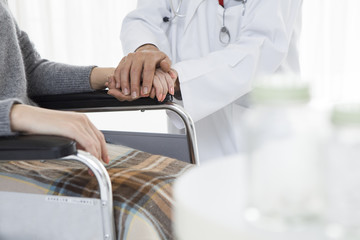 Doctor holding the hand of a wheelchair patient