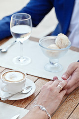 woman's and man's hands holding in cafe with ice-cream and coffe