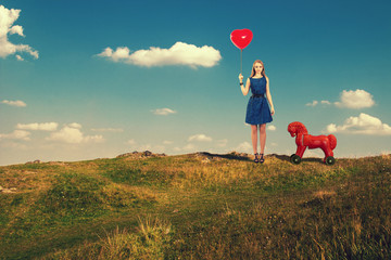girl with a ball in hand and with a toy horse walks outdoors.