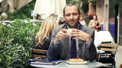 Portrait of happy, confident businessman drinking coffee in cafe
