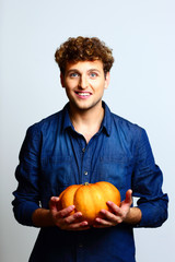 Happy man holding pumpkin over blue background