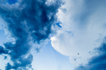 Blue sky with dark and white clouds and two birds