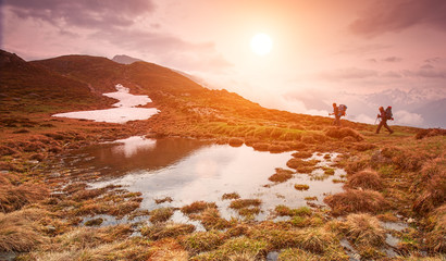Two hiking in the mountains in beautiful morning at a small lake