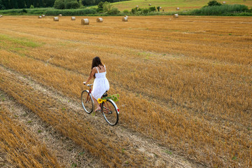 Beautiful woman with old bike in the wheat field