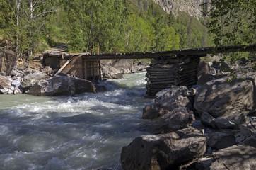 Old dilapidated bridge on the mountain rive