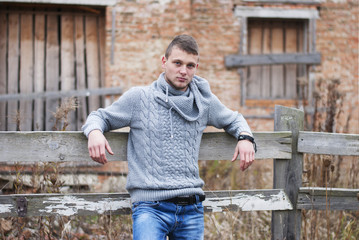 man in knitted sweater standing near the fence