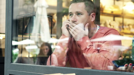 Attractive, young man talking on cellphone in cafe