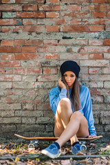 Teenager intimate portrait sit on skateboard against brick wall.