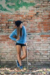 Full body teenager portrait with skateboard against brick wall.