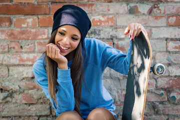 Smiling teenager portrait with skateboard against brick wall.