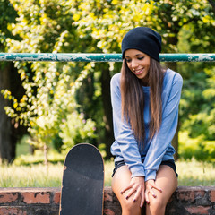 Teenager portrait with skateboard sit on brick wall outdoors in