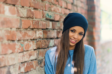 Smiling teenager portrait outdoors against brick wall.