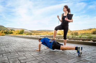 Girl coach training hard a man through push ups