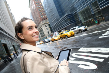 Businesswoman standing in a street of Manhattan with tablet