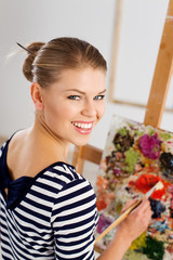 Smiling woman painter with paintbrush standing at easel