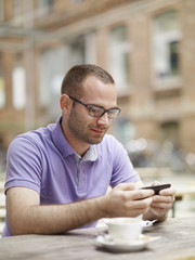 Portrait of a happy young man sitting outdoors with mobile phone