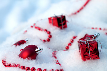 Red Christmas ornaments lie on the snow in winter