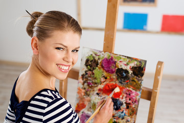 Young smiling female with paint brush and palette working