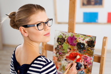 Thinking girl artist with color palette and brush in studio