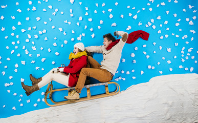 Young couple on sledge having fun
