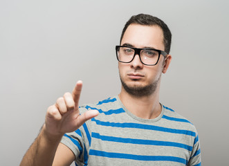 young man in glasses clicks index finger in the space
