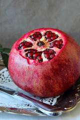 Ripe pomegranate with sliced tip on a platter.