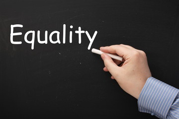 Hand writing the word Equality on a blackboard