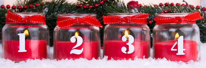 vierter advent mit roten kerzen im glas