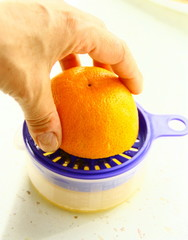 main qui presse  une orange,jus d'orange frais
