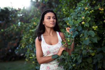 girl peeking from behind apple-tree