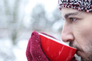 Mann trinkt heißen Tee im Winter