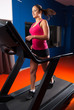 Beautiful smiling girl running on treadmill in the modern gym