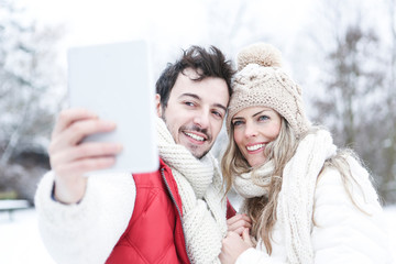 Paar im Winter fotografiert sich mit Tablet PC