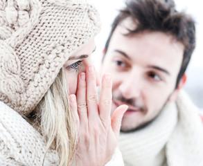 Frau weint neben Mann im Winter