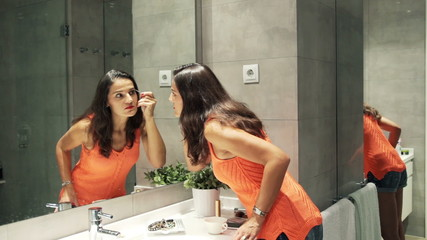 Woman plucking eyebrows with tweezers in front of the mirror in