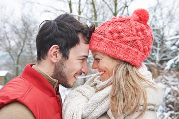 Paar im Winter steckt Köpfe zusammen