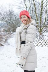 Lachende Frau steht im Winter im Schnee