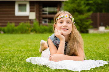 teen girl with a wreath of flowers lying on a fresh green grass