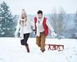 canvas print picture - Glückliches Paar zieht Schlitten im Schnee