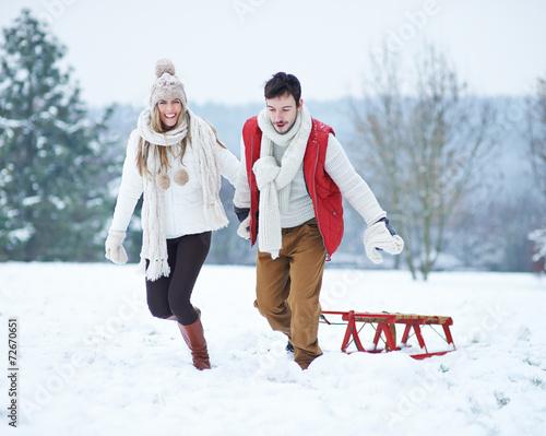 canvas print picture Glückliches Paar zieht Schlitten im Schnee