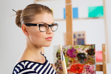 Working woman artist with paintbrush in artistic studio