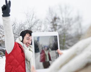 Frau fotografiert Mann mit Tablet Computer
