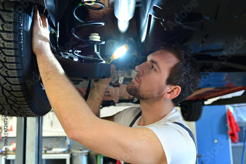 Leinwandbild Motiv Automechaniker // Mechanic checks a vehicle