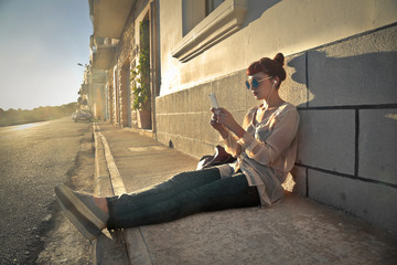 Girl sitting in the sun and using her phone