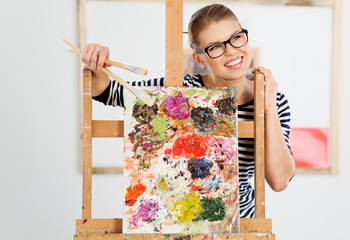 Joyful female artist in eyeglasses holding paintbrushes