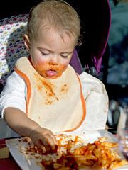 baby girl gets dirty face with tomato eating  pasta