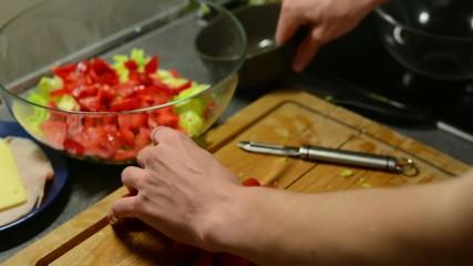 man prepares salad - man sliced tomatoes