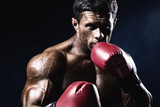 Young man looking aggressive with boxing gloves. Caucasian male