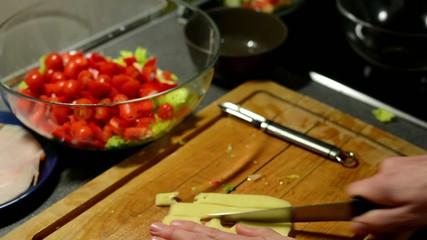 man prepares salad - man sliced cheese