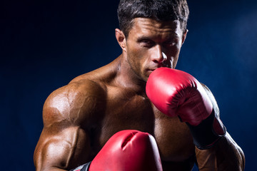 Close-up portrait of boxer in red boxing gloves on a dark blue b